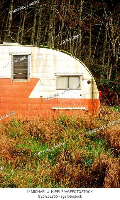 Orange trailer in field. Anderson Island. Puget Sound. Washington. USA