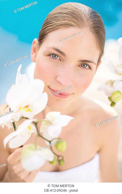 Woman holding flower poolside