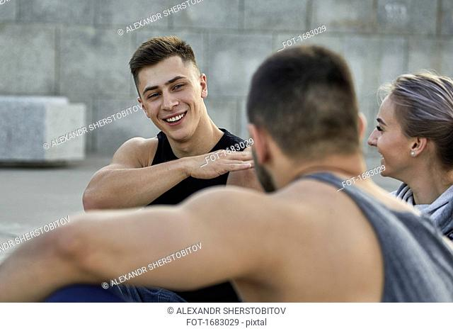Happy young male athlete gesturing while resting with friends on footpath