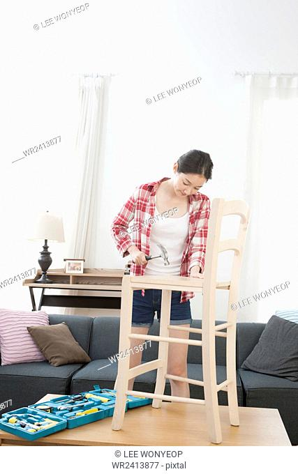 Young woman fixing a chair