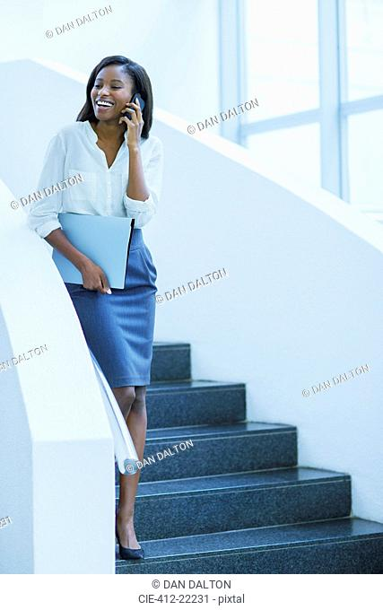 Businesswoman walking on cell phone on stairs of office building