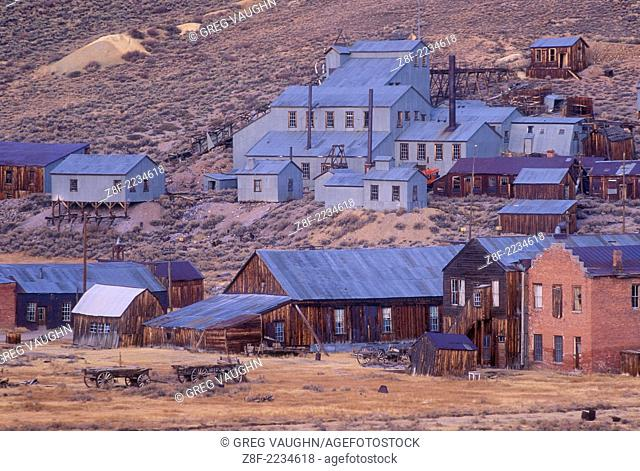 Bodie ghost town at dusk with old Standard Stamp Mill buildings on hillside; Bodie State Historical Park, California