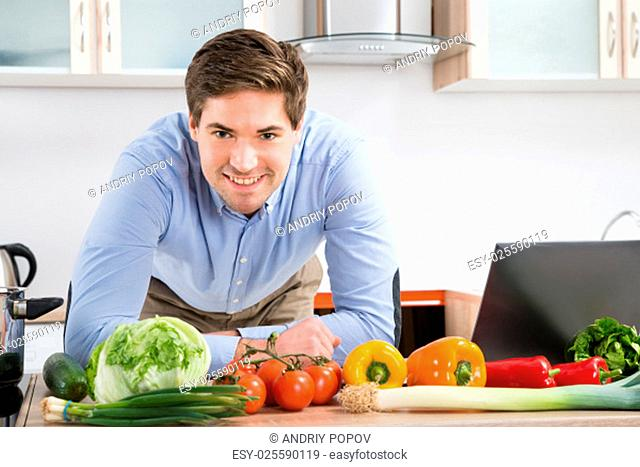 Happy Man Leaning On Kitchen Counter With Laptop And Vegetables In Kitchen