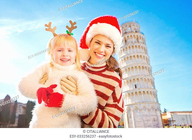 Portrait of happy mother in Christmas hat and daughter wearing funny reindeer antlers standing in front of Leaning Tour of Pisa, Italy
