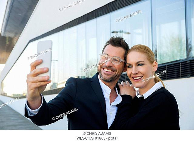 Smiling businessman with woman taking a selfie