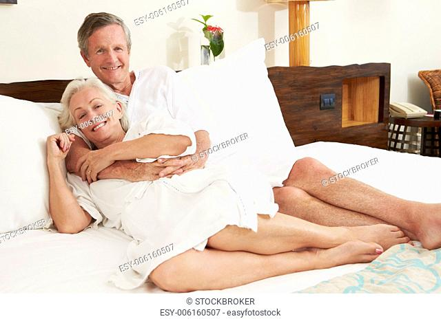Senior Couple Relaxing In Hotel Room Wearing Robes