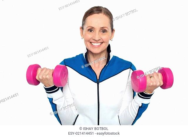 Happy woman carrying dumbbells in both hands