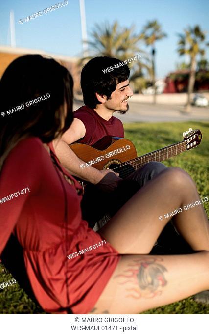 Spain, Barcelona, smiling young man playing guitar for girlfriend sitting on a meadow