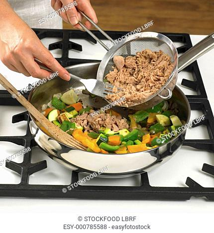 Sweating vegetables and tuna in a frying pan