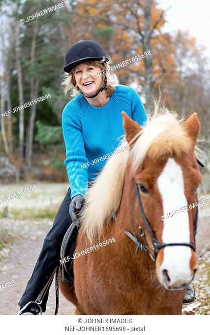 Senior woman riding on Icelandic horse