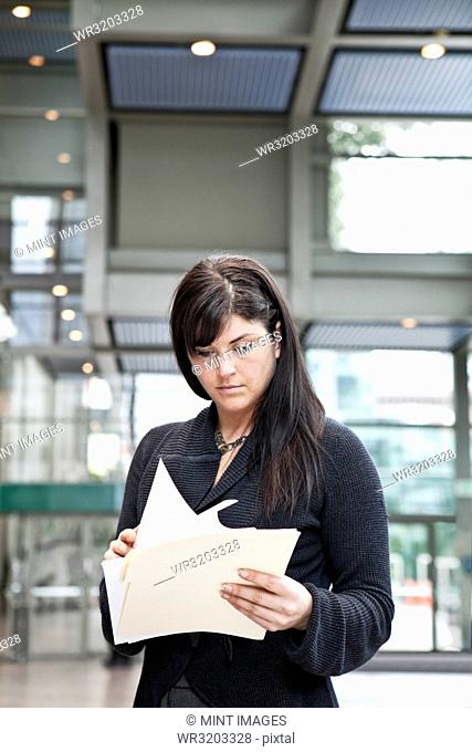 A young Caucasian businesswoman going through paperwork in a convention centre lobby area