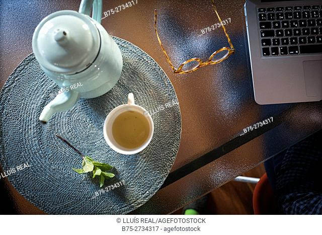 Overhead view of glass table with a teapot, a cup of tea, mint leaves, glasses and laptop computer