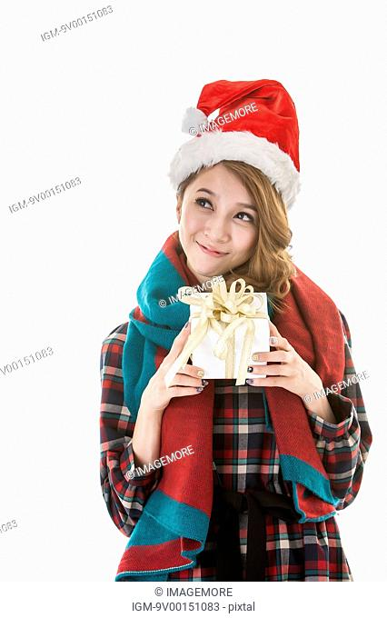Young woman holding Christmas gift, wearing Christmas hat