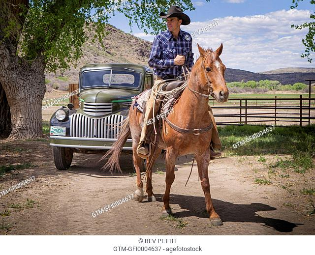 Cowboy riding horse near old antique truck