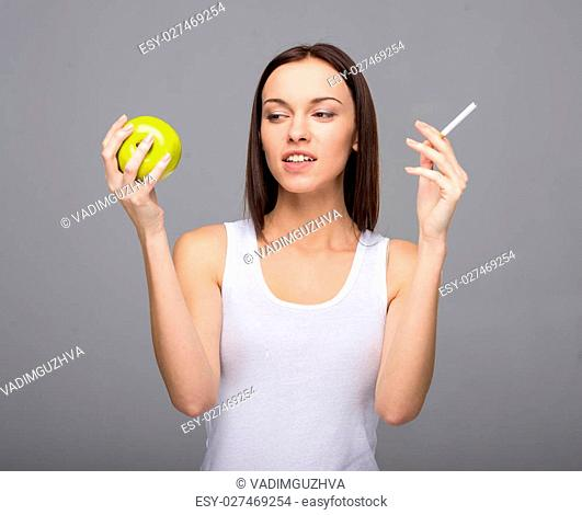 Difficult choice. Young woman with apple and cigarette