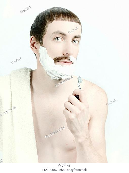 young man shaving with towel on the shoulders