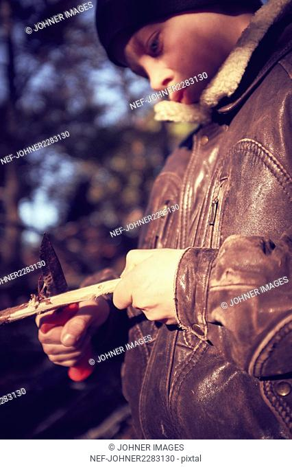 Boy whittling stick