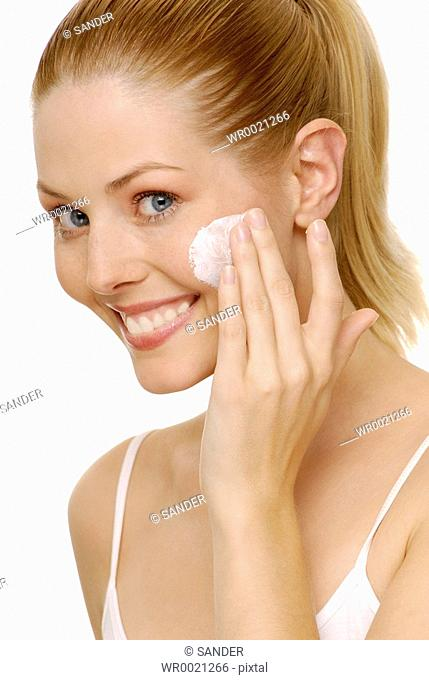 Portrait of woman applying moisturizer on her cheek and smiling