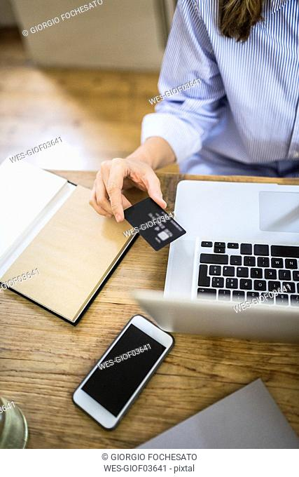 Close-up of woman at wooden desk with credit card and laptop