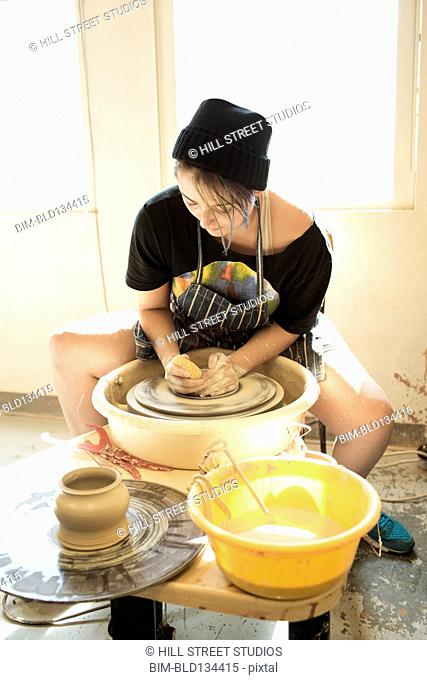 Mixed race student throwing pottery on wheel