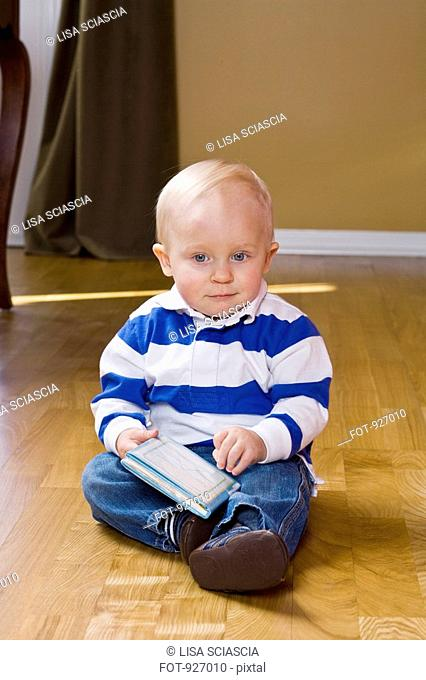 A toddler sitting on the floor, holding a book