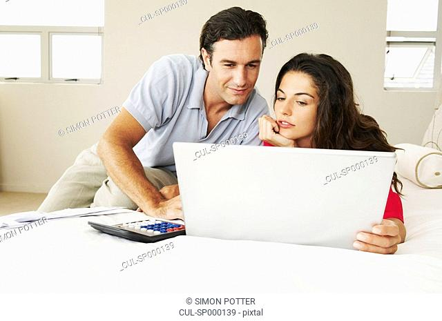 Couple discussing bills on bed