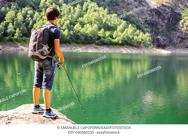 boy fishing in the high mountains in alpine lake, on a summer day, italy piedmont valley ossola