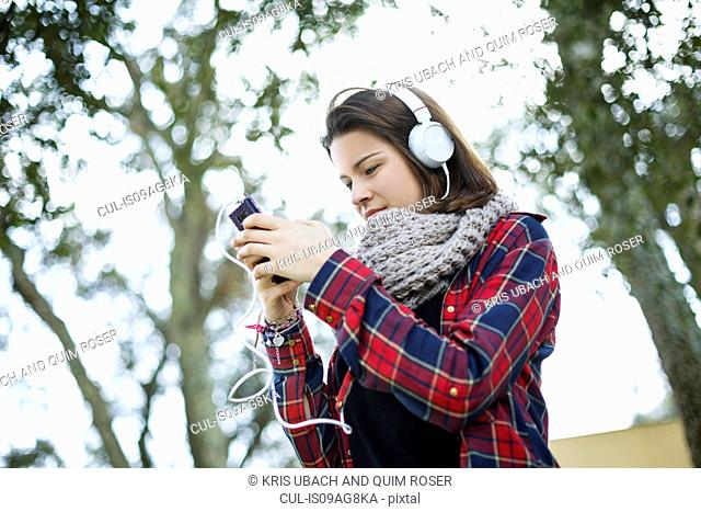 Teenage girl using mp3 in forest