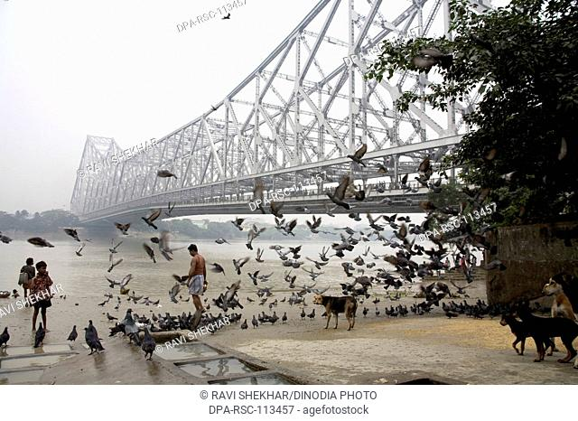 Activities on Babu ghat ; Howrah bridge over Hooghly river in background ; Calcutta now Kolkata ; West Bengal ; India