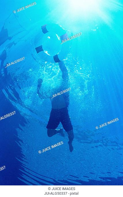 Underview, man swimming, holding onto life preserver