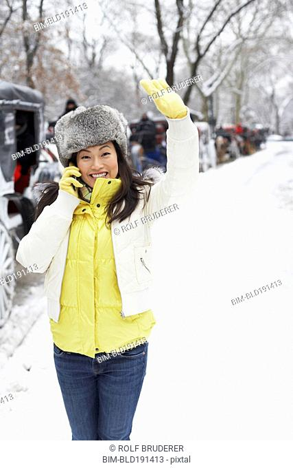 Korean woman talking on cell phone on snowy day