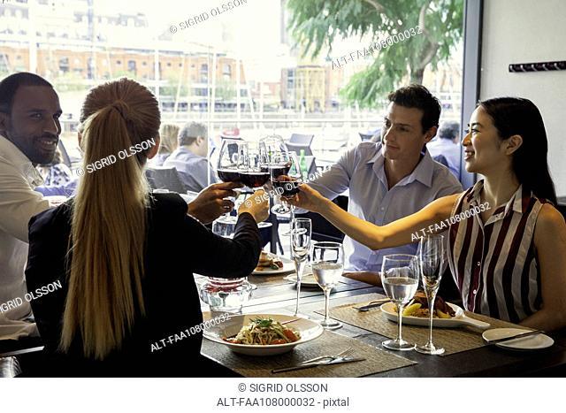 Friends clinking wine glasses in restaurant