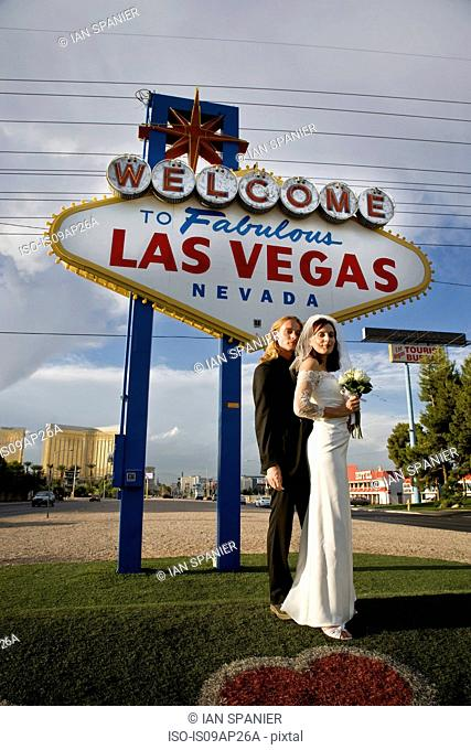 Portrait of newly married couple in front of the welcome to Las Vegas sign, Nevada, USA