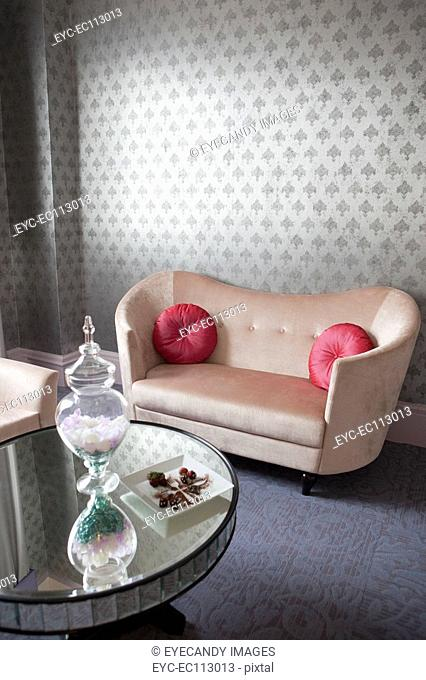 Coffee table and couch in a living room with wall to wall carpeting and wall paper