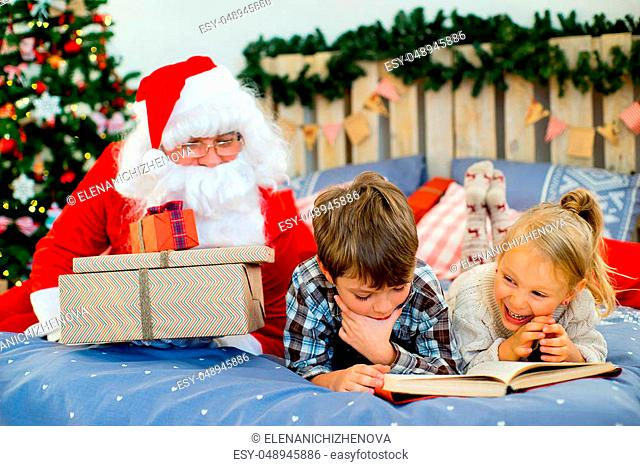Santa Claus quietly came to the children who are reading a book while lying on decorated bed with Christmas tree in the background