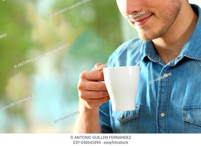 Close up portrait of a relaxed man holding a hot drink cup at home