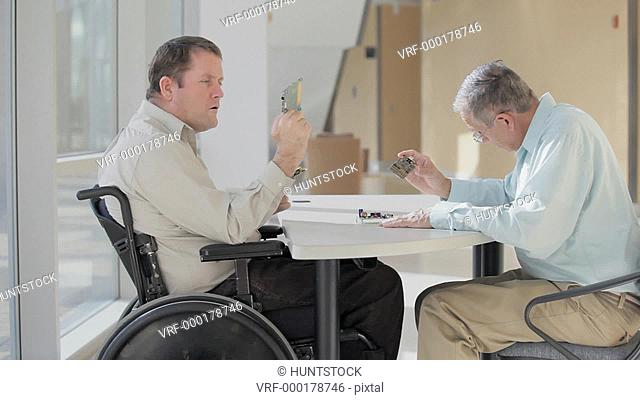Quadriplegic electronic engineer struggling to use his hands to hold circuit boards during design review