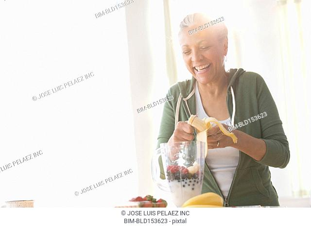 Older Hispanic woman making fruit smoothie