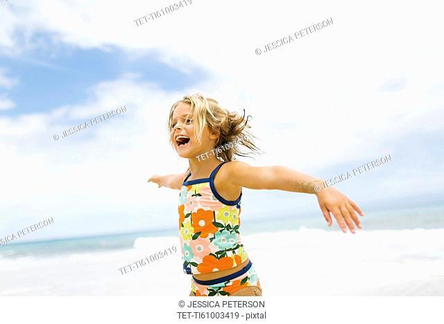 Girl (6-7) spinning on beach
