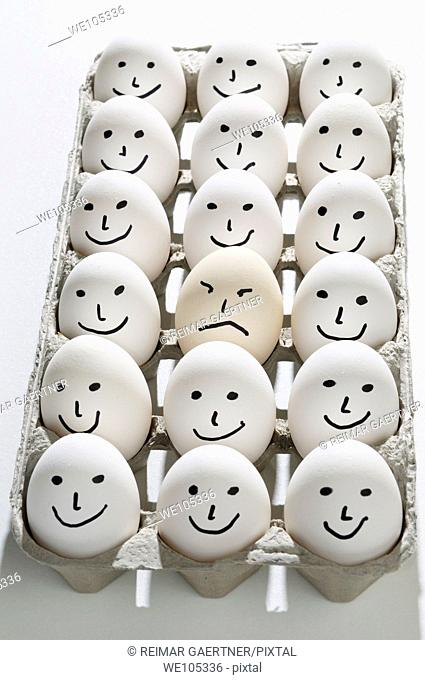 Package of bright backlit eggs with smiling faces except for one grumpy sad face