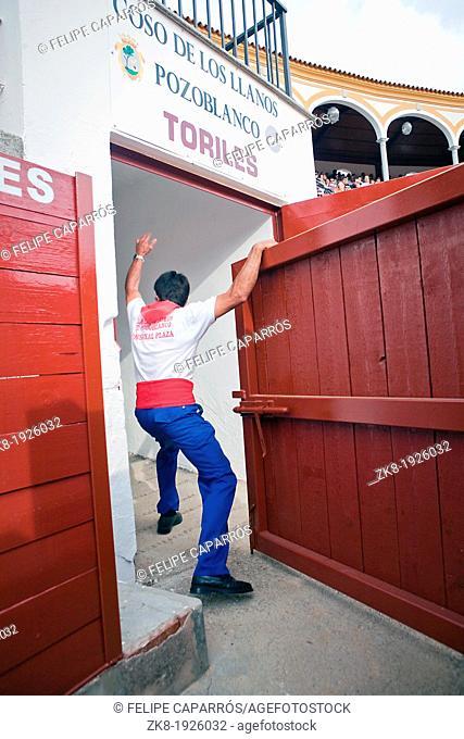 Employee of the bullring opens the door of bullpens, Pozoblanco, Spain