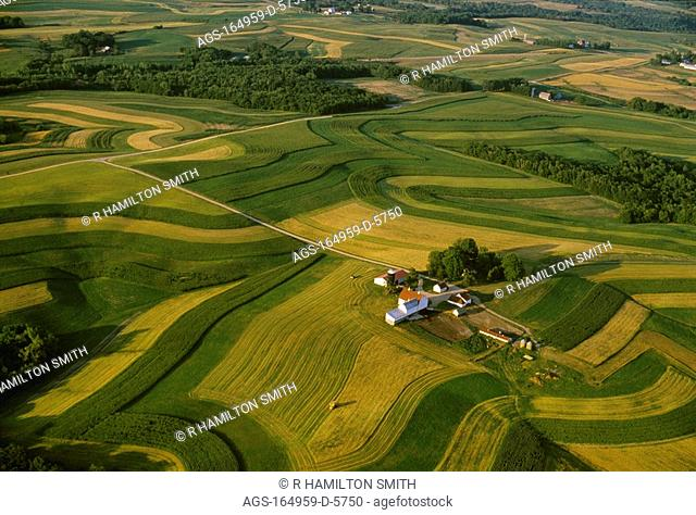 Agriculture - Aerial view of a farmstead surrounded by contour strips of alfalfa, corn and oats / WI