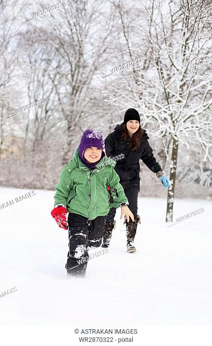 Happy mother and son running on snow field