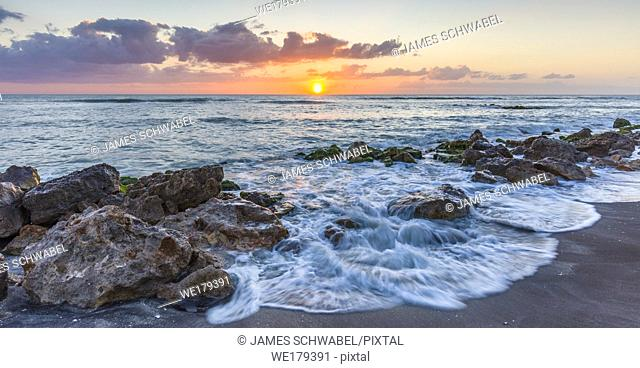 Sunset over the rocky shore of the Gulf of Mexico at Caspersen Beach in Venice Florida