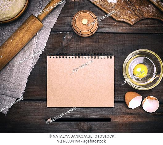 empty paper notebook with brown pages to record a recipe for dough dishes, next to an egg and a kitchen roll, top view