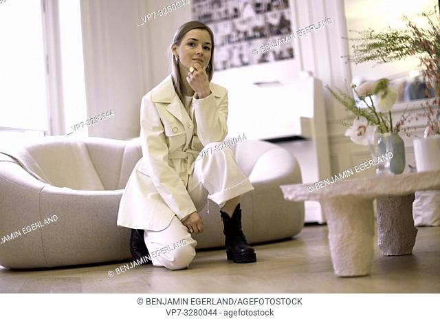 cool fashionable woman posing in living room during fashion week, in Paris, France