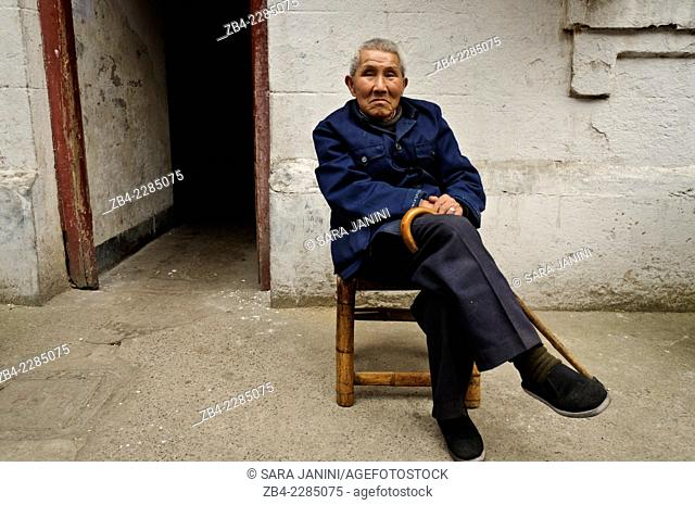 A local man sitting at the fron of his house, old district, Shanghai, China, Asia