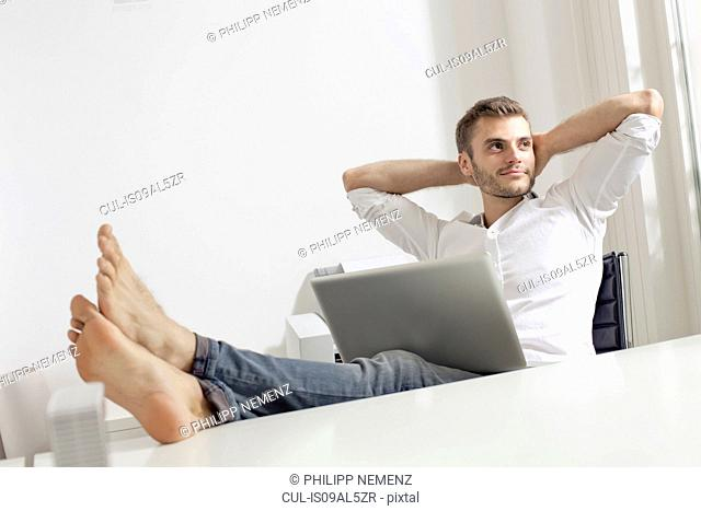 Young man with laptop relaxing