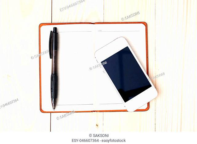 Small notepad with pen and smartphone on wood background