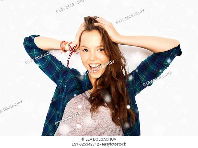 winter, christmas, people, hair care and teens concept - happy smiling pretty teenage girl touching her head over gray background and snow